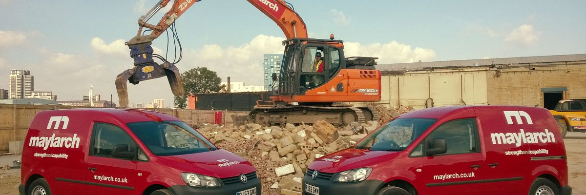 two vans in front of a digger