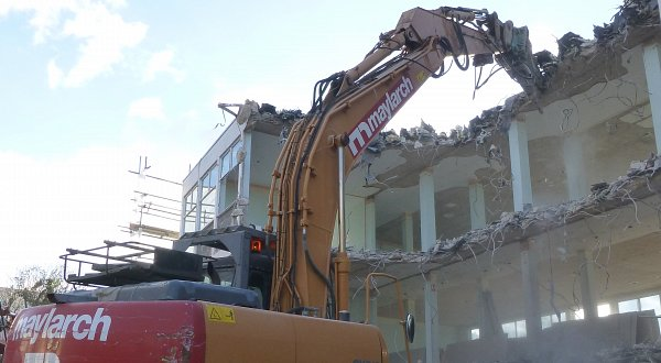 Excavator demolishing building in Cheltenham